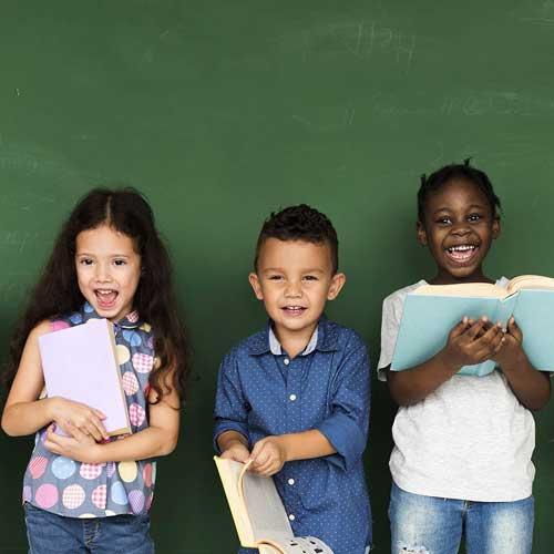 Children standing in front of blackboard holding books