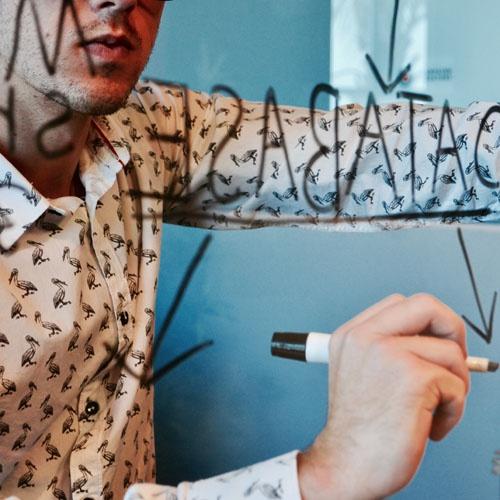 Man writing on transparent board