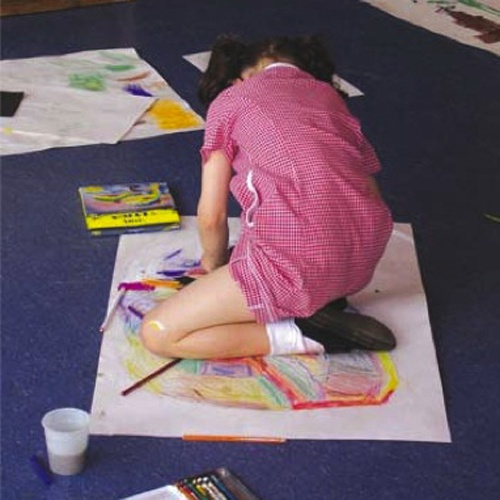 Child sat on floor on top of paper drawing with colours