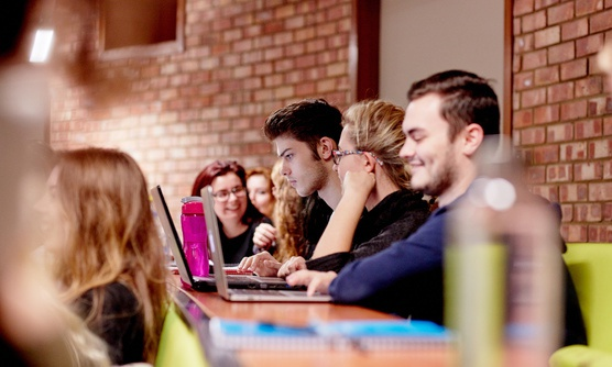 A row of students concentrate on work during a lecture.