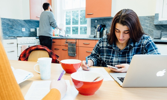 A student studies in her accommodation kitchen