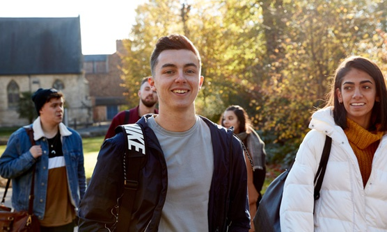 A group of students walk on campus, one smiles at the camera