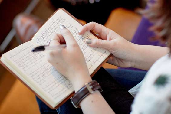 Student writing in notebook in lecture