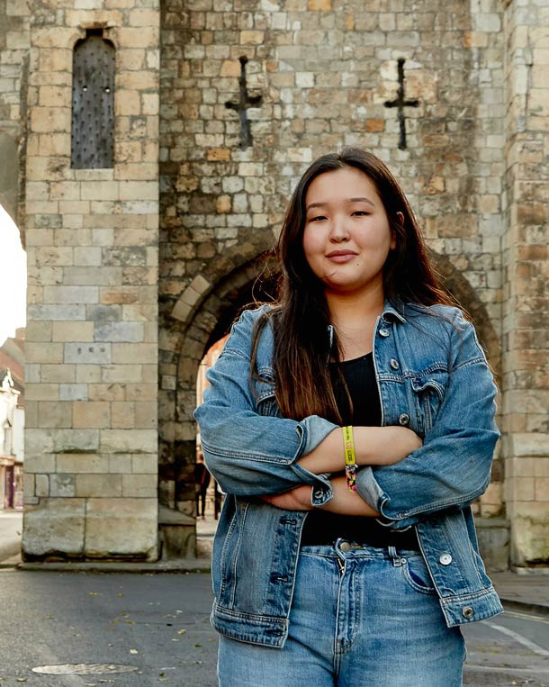 A student folds her arms and smiles at the camera. York's medieval city walls are in the background.