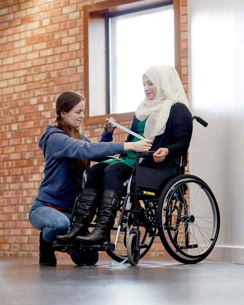 Student measuring wheelchair with tape measure