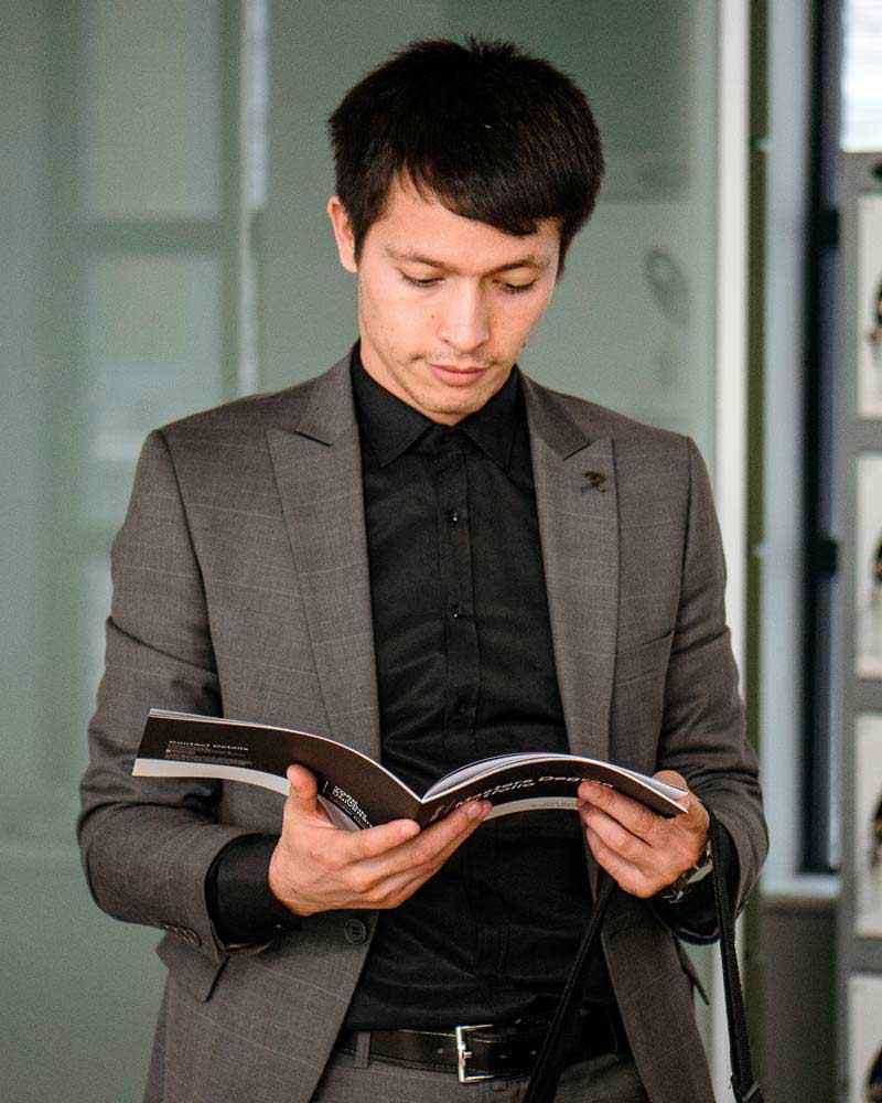 Business student looking at brochure, wearing suit