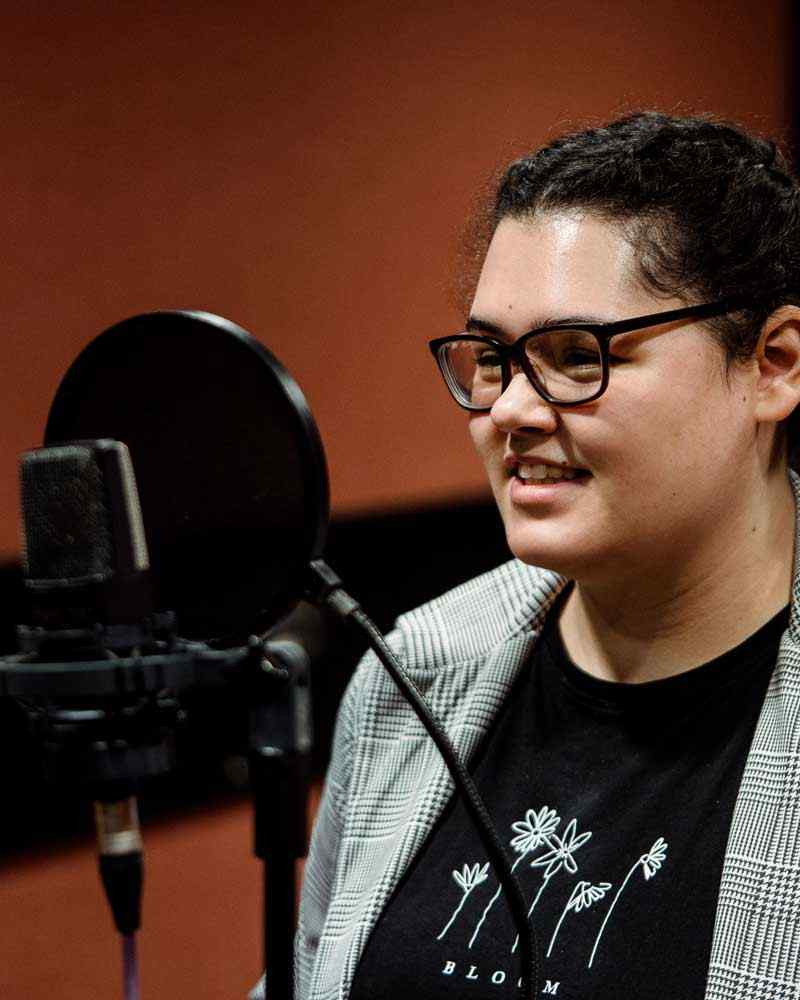 Student singing into recording microphone