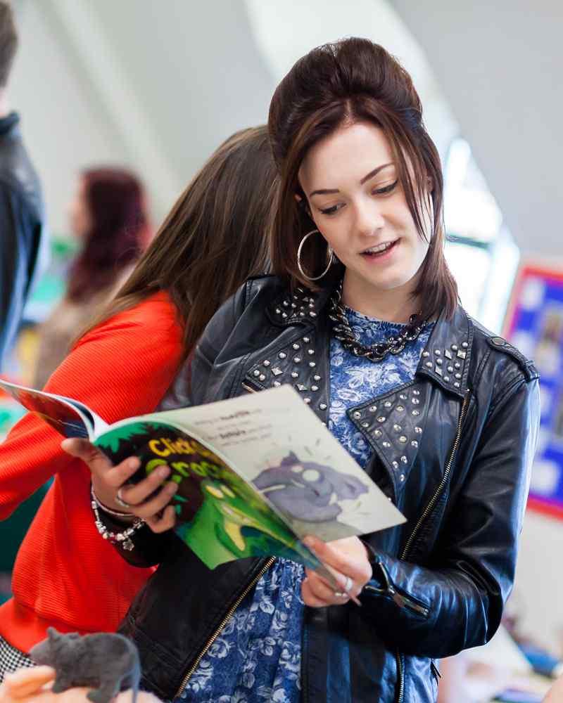 A PGCE student reading a children's book
