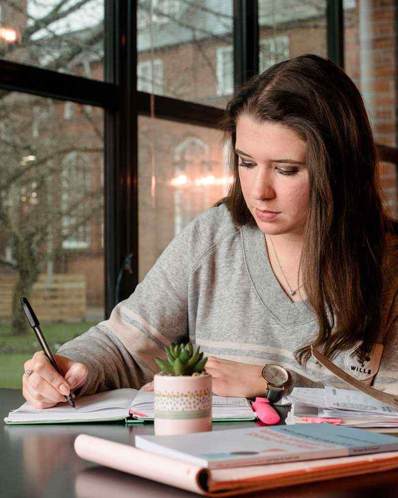 Student writing in notebook in Students' Union