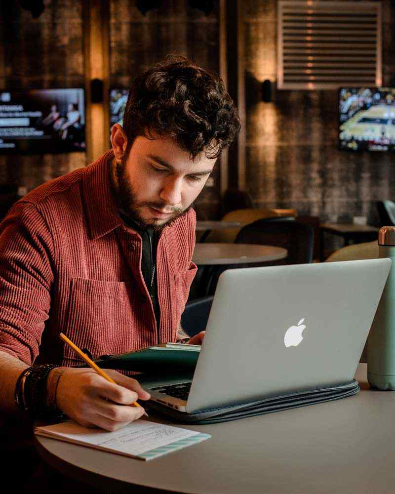 Student taking notes from laptop