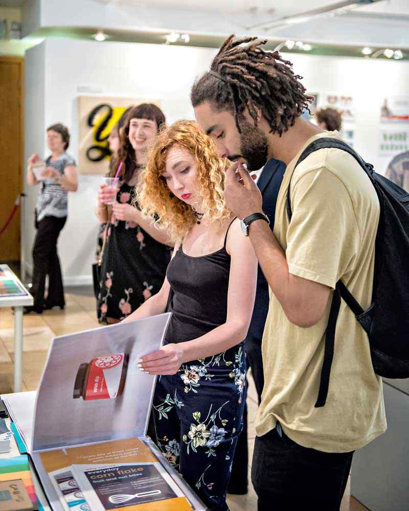 Students looking at porfolio at graphic design show