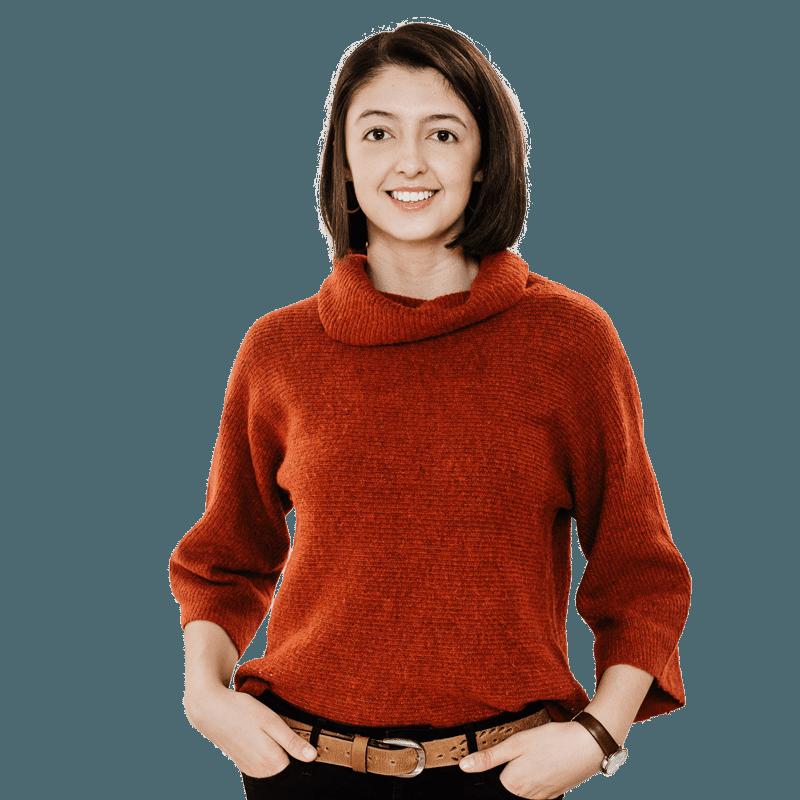 Brunette female student wearing red jumper, smiling at camera, hands on her hips