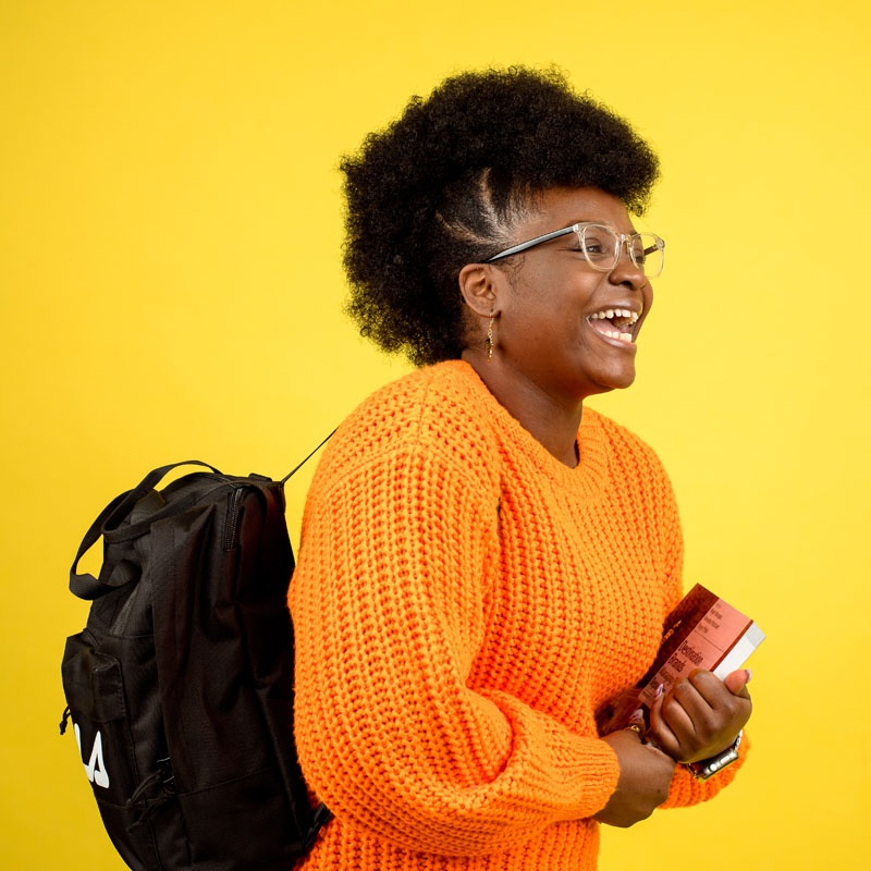 Student smiling holding folder in front of yellow background